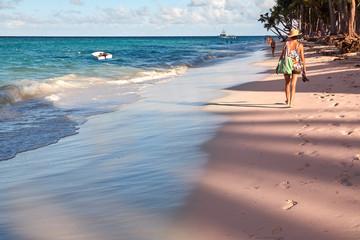 Girl walking down the beach of Punta Cana, holiday resort. Dominican Republic.