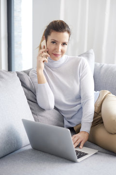 Managing her business from home. An attractive middle aged woman using her cell phone and making call while sitting on sofa with laptop and working from home office.