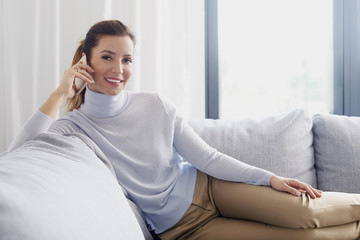 Attractive mature woman talking with somebody on mobile phone while sitting on couch at home