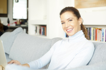 Woman browsing on the internet. Smiling middle aged woman using digital tablet while relaxing on sofa at home.