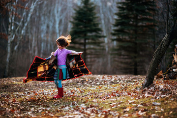 Girl wrapped in a blanket spinning around in forest