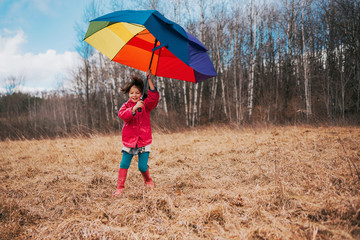 Girl holding an open umbrella on a windy day