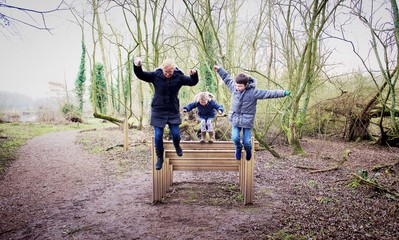 Mother and two children jumping off a wooden steps in forest, Kingsbury, Warwickshire, England, UK
