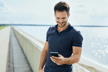 Happy man texting on his phone outdoors