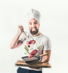 Young cheerful cook man with beard holding a frying pan with steaks and knife flying in the air on light background. Meat food and cooking concept