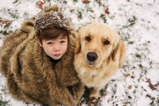 Golden retriever dog and boy wrapped in a blanket sitting in the snow