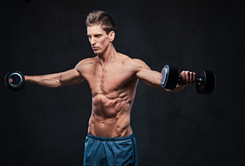 Shirtless athletic male doing shoulders exercises.
