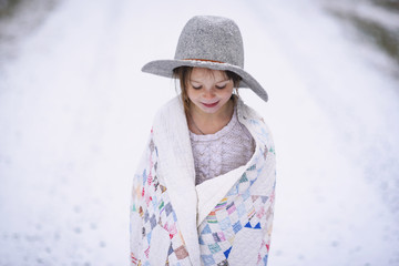 Smiling young girl looking down while standing on snowy landscape