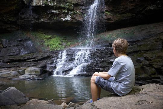 Boy Looking at Waterfall