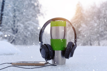 Headphones, smartphone and cup of tea in winter