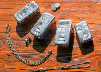 Silver bars, jewelry and coins on the background of mahogany.