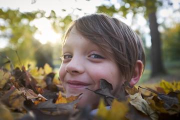 Boy in Pile of Leaves