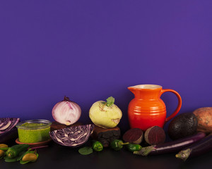 Assortment of raw organic purple and green vegetables on violet background.