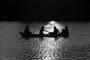 Family in the boat at Daumesnil lake (Paris, France) in sunset glow. Silhouettes. Harmony with nature idea.  Black and white photo.