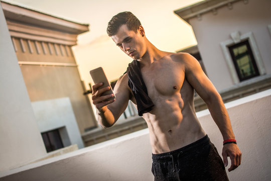 Handsome shirtless man with shirt over shoulders taking a selfie with mobile phone after outdoors training.