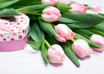 Pink tulips on a white wooden background with a cute heart-gift