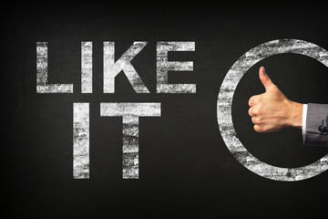 Hand of a businessman showing thumbs up for the phrase LIKE IT written on a blackboard