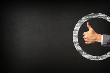 Hand of a businessman showing thumbs up on blackboard background
