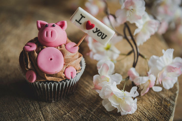 Sweet pig with I love you sign on the top of cup cake,selective focus