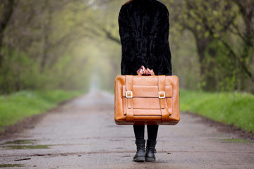 Girl in black coar holding suitcase at countryside