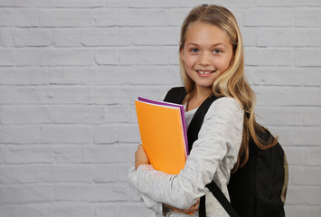 Portrait of happy smiling school girl wearing backpack and books.