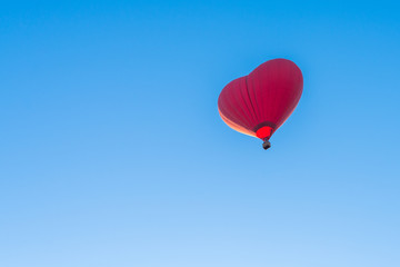 Red air in the form of a heart balloon in the blue sky
