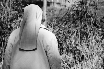 A nun in grey robe in the forest. A game of light and shadow. Religion and nature. Meditation background. Harmony, God in nature idea. Aged photo. Black and white.