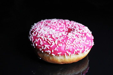 Donut. Beautiful pink donut on black reflective studio background. Isolated black shiny mirror mirrored background for every concept.
