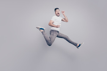 Happiness, freedom, motion and people concept. Shocked, funky, handsome man jumping in air, screaming, shouting with open mouth over grey background
