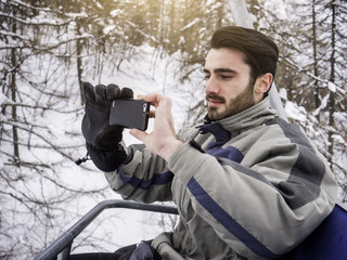 Handsome young man using smarpthone to take photographs of the landscape, while sitting on chairlift among snowy woods in the mountain