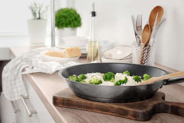 Frying pan with rice and broccoli on kitchen table