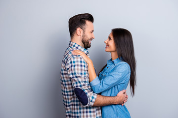 Portrait of caucasian, attractive, smiling couple - bearded man embrace his charming, cute, pretty woman, looking to each other while standing over grey background