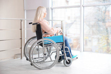 Mature woman in wheelchair indoors