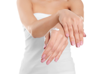 Young woman applying hand cream on white background, closeup