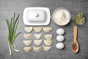 Raw dumplings and ingredients on table, top view