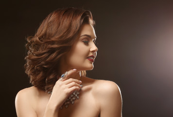 Beautiful woman with elegant jewelry on dark background