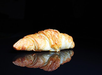 Croissant. Crispy cheesy croissant on black reflective studio background. Isolated black shiny mirror mirrored background for every concept.