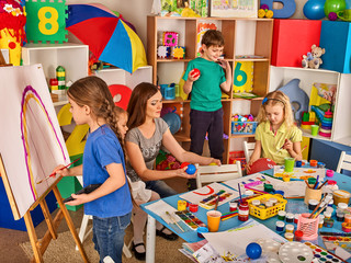 Children painting finger on easel. Group of kids girl and boy with teacher learn paint in class school. Child picture on background. Students draw a rainbow. Newcomer learns at new school.