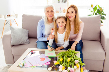 People tenderness comfort gentle gatherings festive parenthood concept. Portrait of charming old aging granny cute sweet preteen writing wish on card and beautiful mum casaul clothe sitting on divan