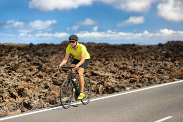 Triathlon biking cyclist man athlete on road bike. Fitness workout outdoors in nature landscape. Male sports competition.