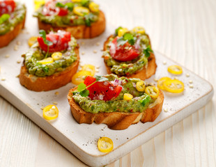 Sandwiches with guacamole, cherry tomatoes, onions, chili peppers and fresh coriander. A delicious and healthy vegetarian appetizer
