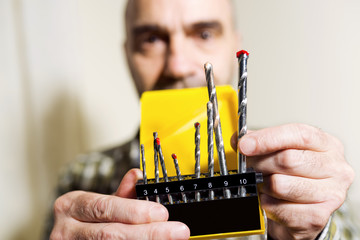 electrician with drill bits for installing radiator