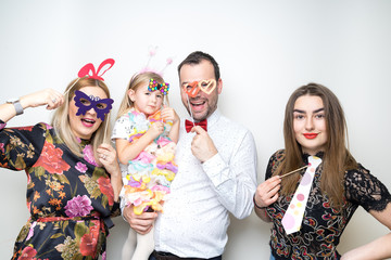young family posing party photo booth props baby girl plain background studio