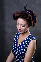 Portrait of beautiful pinup model in blue polka dot dress and bow