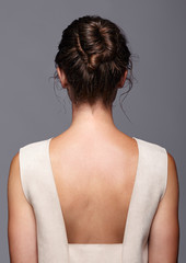 Head and shoulders of a young woman from the back side. Female hair knotted