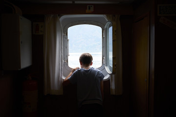 Boy Looking out Porthole of Ship