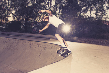 young American man practicing radical skate board having fun enjoying tricks jumps and stunts in concrete half pipe skating track