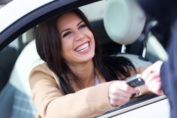Car rental agency employee giving car keys to beautiful young woman.