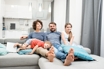Happy family of four sitting on cozy sofa and watching their favorite TV program, interior of modern studio apartment on background