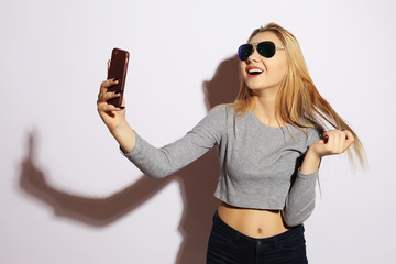Pretty hipster girl making selfie over white background.